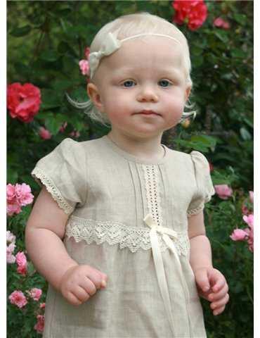 söt flicka i sin dopklänning i trädgård