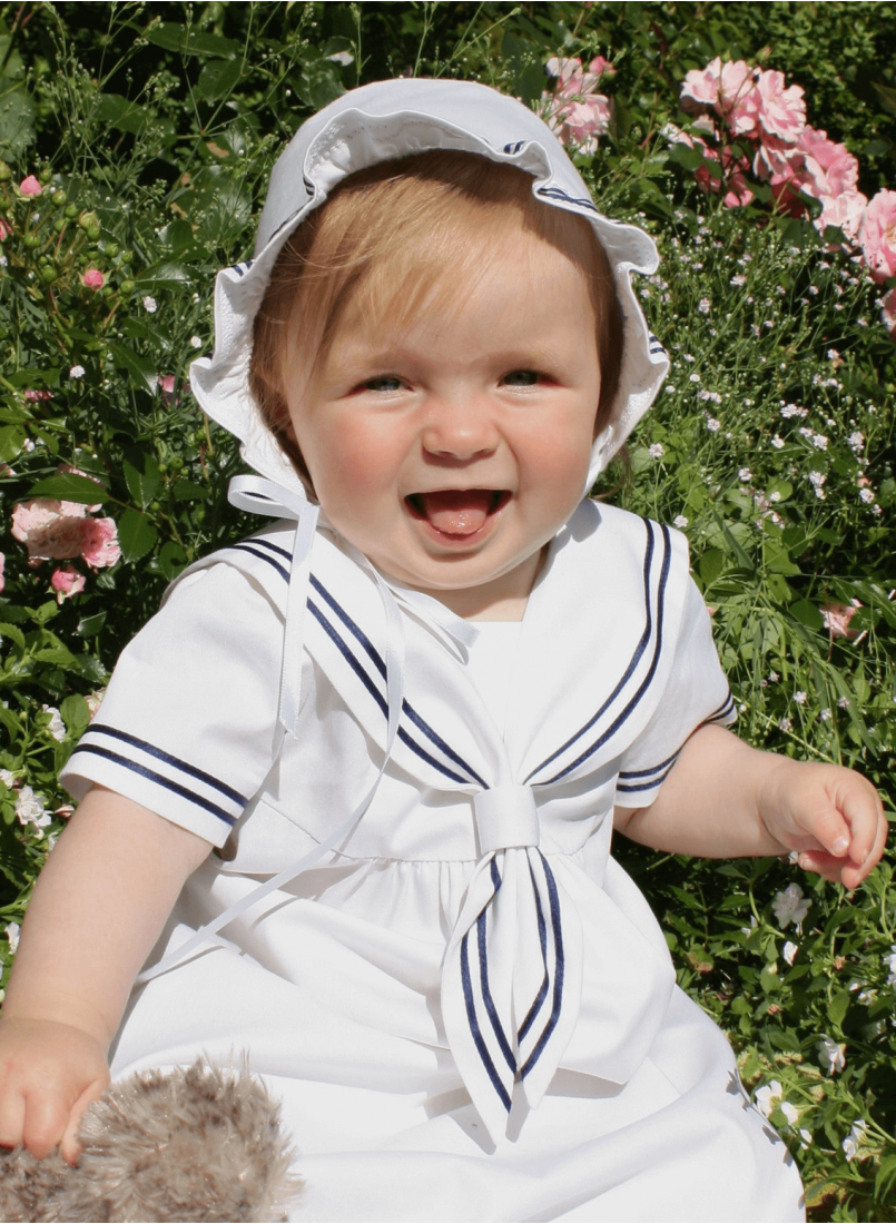 baptism child with a bonnet and sailor's dress