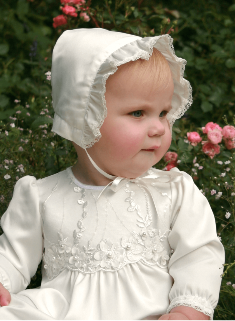 Baptism cap in bright satin from the grace of Sweden with a cute girl