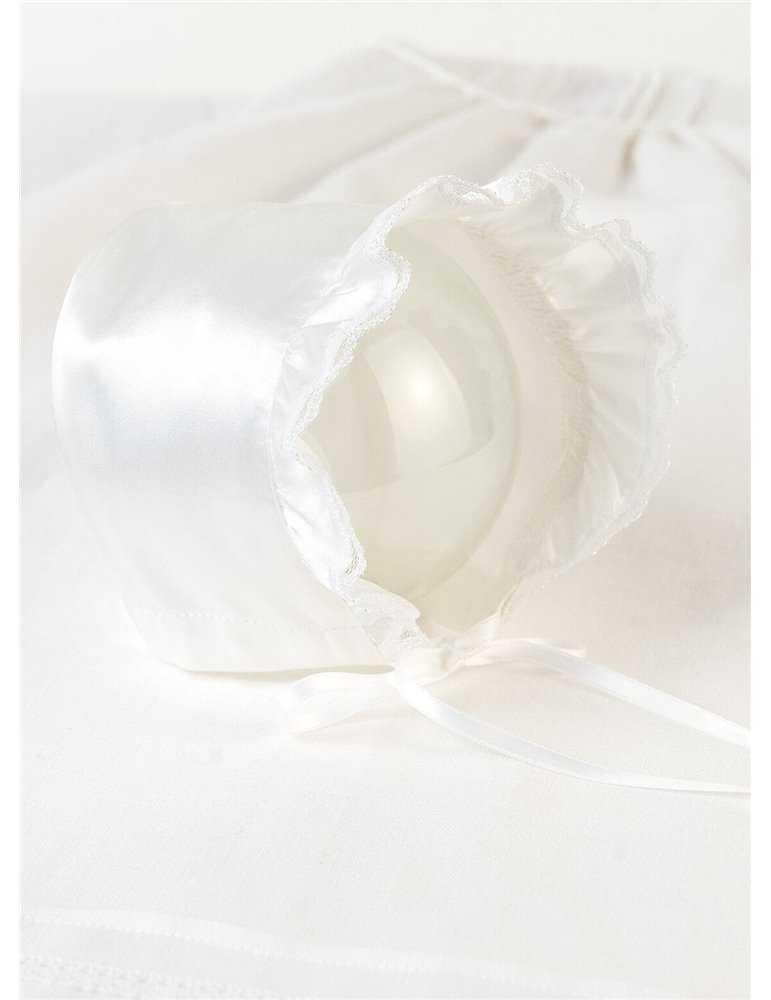 söt pojke med down syndrom i sin dopklänning