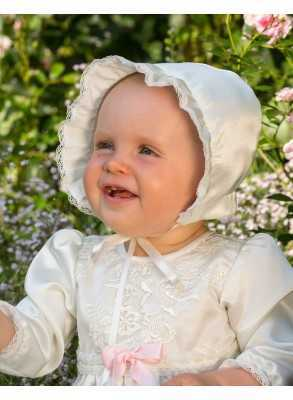 sweet girl in christening bonnet in off white satin